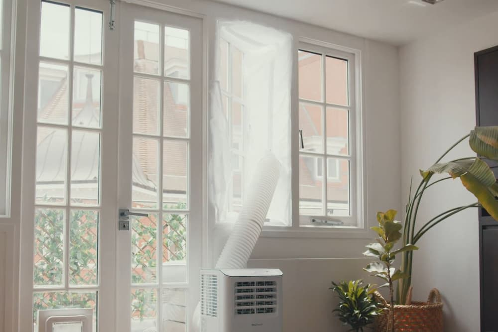 venting portable AC thru hinged window with fabric screen